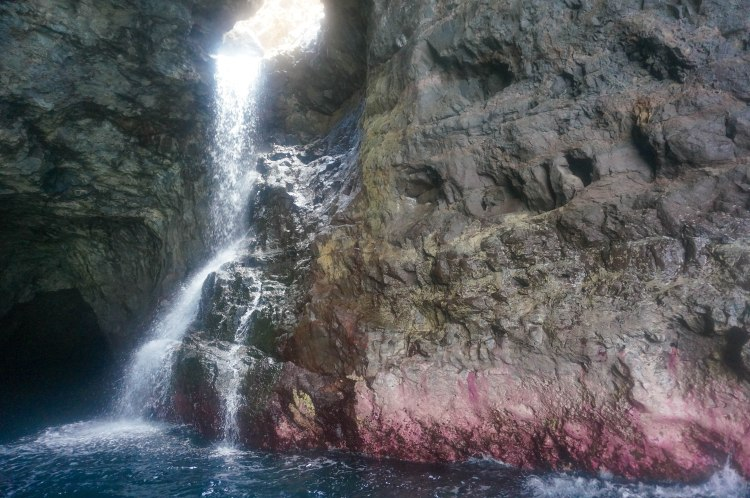 Waterfall flowing through the inside of sea cave.